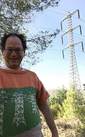 Sam Barsky poses with pylons. This sweater depicts Israeli pylons, which he aesthetically prefers. (Courtesy/Facebook)
