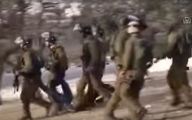 IDF troops carry a Palestinian teen who later died of a gunshot wound during a violent protest near Bethlehem on January 16, 2017. (screen capture: YouTube)