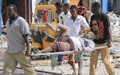 Somali men carry a civilian who was wounded in a suicide car bomb attack on a hotel in Mogadishu, Somalia, Wednesday, January 25, 2017. (AP Photo/Farah Abdi Warsameh)