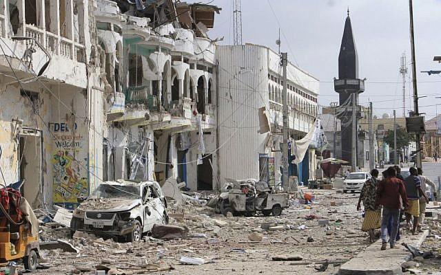 Somalis walk near a hotel and cars destroyed by a car bomb in Mogadishu, Somalia, on Wednesday, January 25, 2017. (AP Photo/Farah Abdi Warsameh)