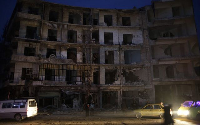 People walk next to a destroyed building in the once rebel-held Shaar neighborhood in the eastern Aleppo, Syria, January 17, 2017. (AP Photo/Hassan Ammar)