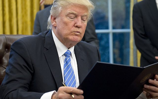 President Donald Trump reading the first of three executive orders he signed in the Oval Office, January 23, 2017. (Ron Sachs/Pool/Getty Images)