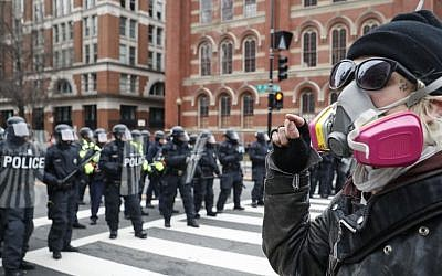 A protester faces off with a line of riot police during a demonstration after the inauguration of President Donald Trump, Friday, Jan. 20, 2017, in Washington. (John Minchillo/AP)