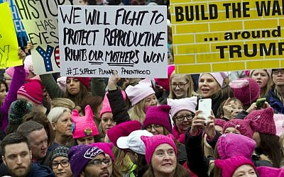 Women with bright pink hats and signs gather to make their voices heard on the first full day of Donald Trump's presidency, Saturday, Jan. 21, 2017 in Washington. (AP Photo/Jose Luis Magana)