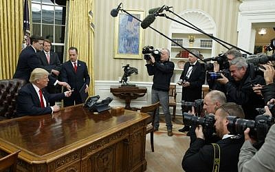 President Donald Trump hands over his pen after signing his first executive order, Friday, Jan. 20, 2017, in the Oval Office of the White House in Washington. (AP/Evan Vucci)