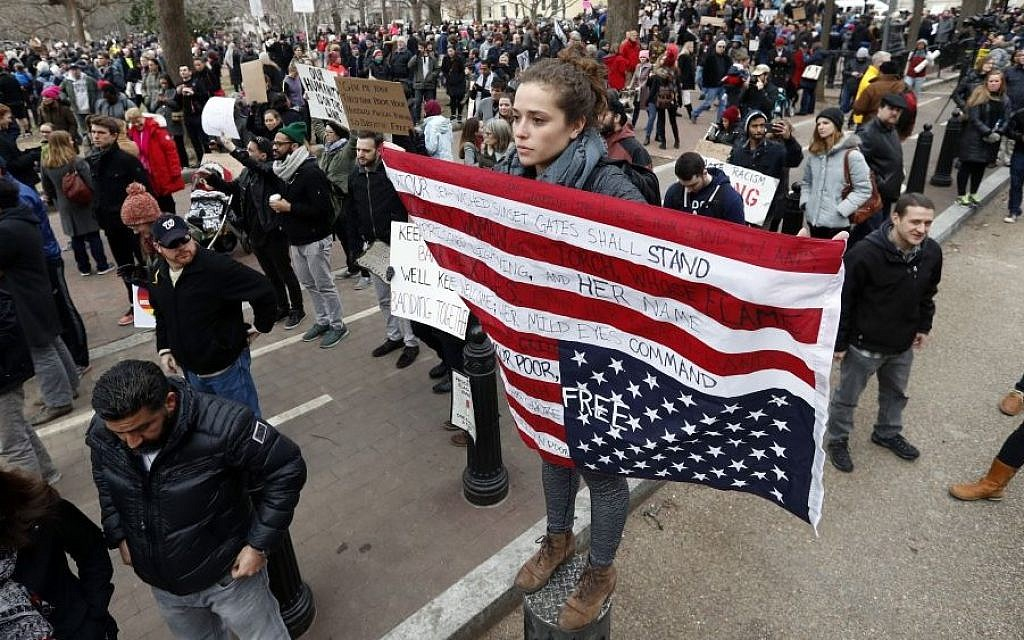 Liz Glusman, from Washington, joins a crowd protesting in Lafayette Park near the White House during a demonstration to denounce President Donald Trump's executive order that bars citizens of seven predominantly Muslim-majority countries from entering the US on Sunday, Jan. 29, 2017, in Washington. (AP /Alex Brandon)