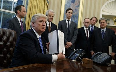 President Donald Trump shows off a signed executive order to reinstitute a policy barring any recipient of US assistance from performing or promoting abortions abroad with money they receive from non-US sources,  January 23, 2017. (AP Photo/Evan Vucci)
