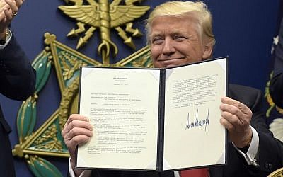US President Donald Trump shows his signature on an executive action on rebuilding the military during an event at the Pentagon in Washington, Friday, Jan. 27, 2017. (AP Photo/Susan Walsh)