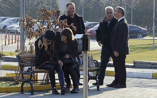 Lebanese Mireille Musalam, sitting left, who lost her husband Haikal Musalam in a terror attack the previous day at a popular nightclub in Istanbul, is surrounded by family members outside a morgue in the city, Monday, Jan. 2, 2017. (AP Photo/Omer Kuscu)