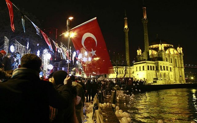 People, some holding Turkish flags, let balloons and lanterns loose into the air in Istanbul's Ortakoy district by the Bosphorus during New Year's celebrations early Sunday, Jan. 1, 2017. (AP Photo/Emrah Gurel)
