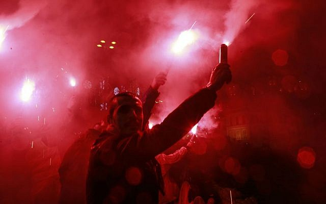 Istanbul revelers light flares shortly after midnight in Ortakoy district by the Bosphorus during New Year's celebrations early Sunday, Jan. 1, 2017. (AP Photo/Emrah Gurel)