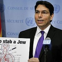 Illustrative: Israel's UN ambassador Danny Danon teaches reporters how to stab a Jew, with a teaching aid commonly found in Palestinian schools. (Loey Felipe)