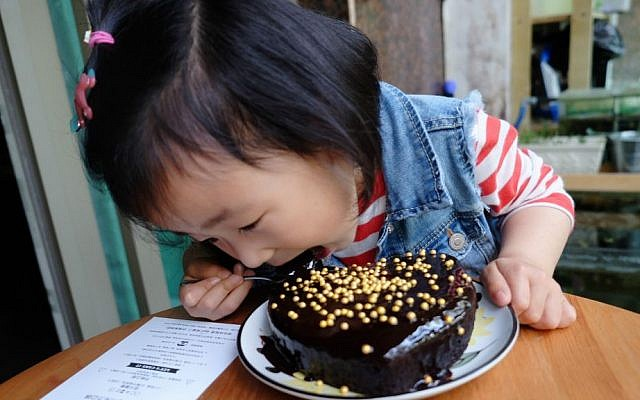Chinese child eating a home baked UgaUga cake. Picture was uploaded by users on UgaUga's blog on WeChat (Courtesy)