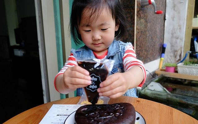 Chinese girl uses UgaUga kit to bake a cake using a rice cooker. Pictures were uploaded to UgaUga's blog by users of the cake kit (Courtesy)
