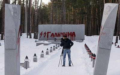 A Nazi symbol is seen painted on a memorial stone at a cemetery where Poles are buried in Bykivnia near the capital Kiev, Ukraine, Wednesday, Jan. 25, 2017. The inscription reads SS Galitchina, a reference to the Galicia division of the Nazi SS organization made up mostly of ethnic Ukrainian volunteers during WW II (AP Photo/Efrem Lukatsky)