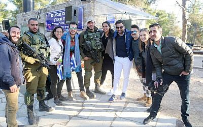 Joseph Waks, fourth from the right, posing with Jewish visitors and soldiers at the Oz Vegaon tent outpost in the West Bank, January 2, 2017. (Bobby Weitzner)