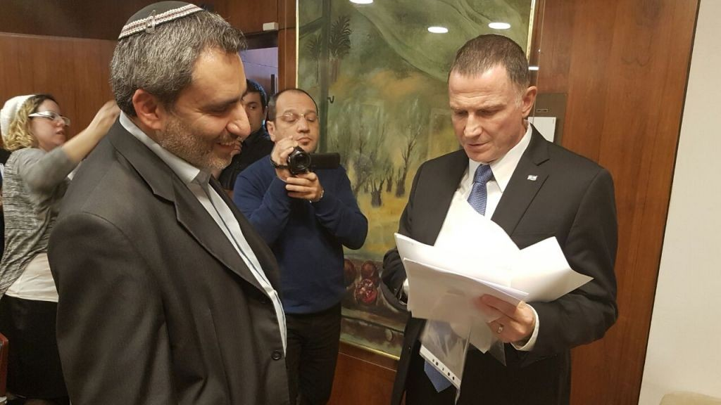 Yuli Edelstein, right, reviewing signatures of 72 MKs supporting a vote on the impeachment of Basel Ghattas, as Zeev Elkin, left, looks on, in the Knesset on January 16, 2017. (Knesset Spokesman's Department)