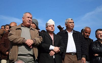 MK Ayman Odeh (center) of the Joint List and other Arab Israeli leaders stand at the scene of fatal clashes in the Bedouin village of Umm al-Hiran, in which Odeh was injured, on Wednesday, January 18, 2017 (courtesy)