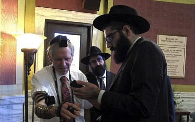 Rabbi Berry Nash, right, prays as Montana Rep. Dave Fern, R-Whitefish, wears boxes containing Torah versus called Tefillin on Wednesday, Jan. 18, 2017 in Helena, Mont. (AP/Matt Volz)