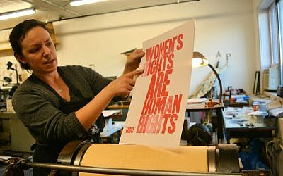 Shelley Barandes examines the poster she is making on an antique letter press for the Women's March on Washington. Barandes, the owner of a design and letterpress print shop in the Boston area, is one of the many American Jews traveling to Washington for the march. (Dina Kraft/Times of Israel)