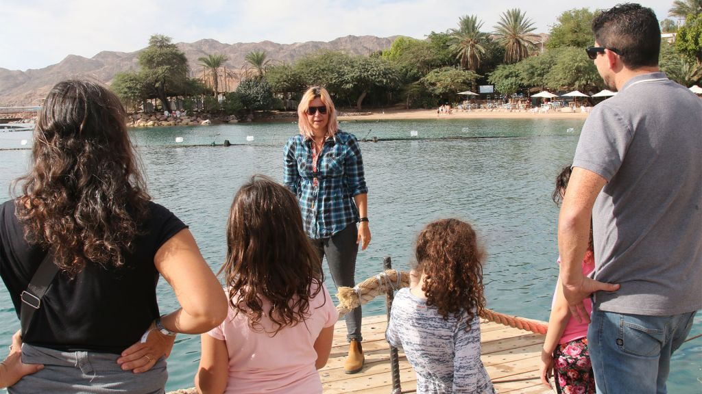 Tal Fisher, head of the Dolphin Team at the Dolphin Reef in Eilat, gives a lesson to interested visitors. (Shmuel Bar-Am)
