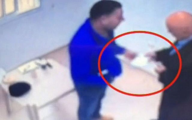 Security camera footage showing MK Basel Ghattas, right, handing an envelope to an inmate in Israeli prison. (screen capture: Channel 10)