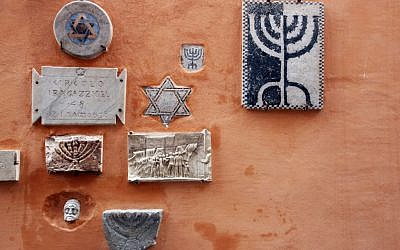 Religious symbols hang on a wall in a public street in Rome's historic Jewish Ghetto. (Getty images)