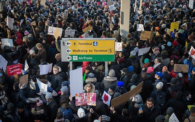 Protesters against Donald Trump's executive order to suspend refugee arrivals and impose tough controls on travelers from Iran, Iraq, Libya, Somalia, Sudan and Syria  gather at  JFK International Airport in New York on January 28, 2017 . (Photo by BRYAN R. SMITH/AFP/Getty Images)