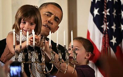 President Barack Obama holding up Kylie Schmitter, 4, to light a menorah as Kylie's sister, Lainey, looks on during a Hanukkah reception at the White House, December 5, 2013. (Alex Wong/Getty Images)