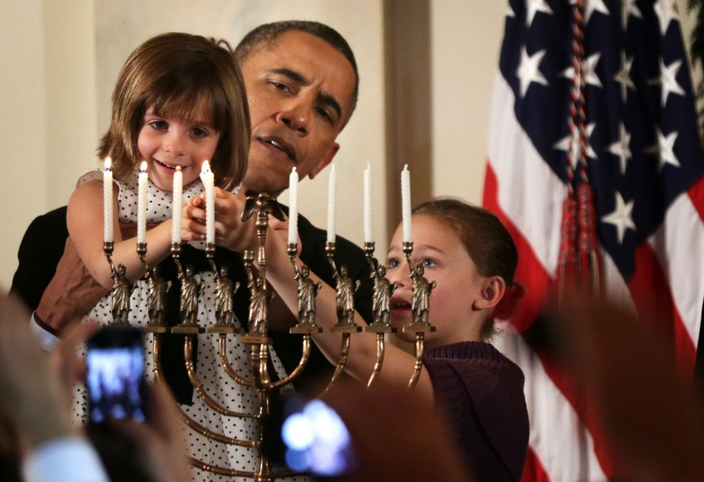 President Barack Obama holding up Kylie Schmitter, 4, to light a menorah as Kylie's sister Lainey looks on during a Hanukkah reception at the White House, December 5, 2013. (Alex Wong/Getty Images/via JTA)