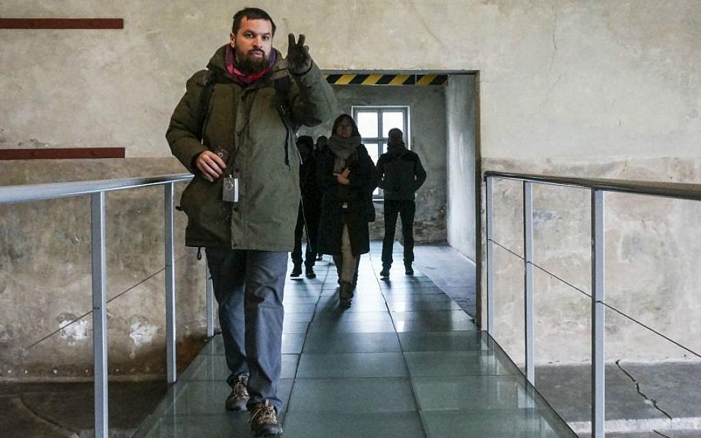 Pawel Sawicki guiding journalists through the so-called central sauna of Auschwitz-Birkenau, December 1, 2016. (Cnaan Liphshiz/JTA)