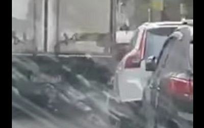A still image taken from a cell phone video shows a truck driving bashing into parked cars on a narrow street in Tel Aviv on January 26, 2017 (screen capture: YouTube)