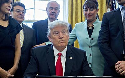 President Donald Trump signing an executive order in the Oval Office of the White House surrounded by small business leaders, Jan. 30, 2017. (Andrew Harrer/Pool/Getty Images)