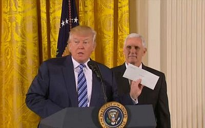President Donald Trump, front, accompanied by Vice President Mike Pence, right, shows a letter left him by his predecessor Barack Obama at a White House senior staff swearing in ceremony in the East Room, Sunday, Jan. 22, 2017, in Washington. (screen capture/AFP video)
