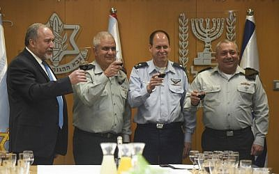 From left, Defense Minister Avigdor Liberman, Maj. Gen. Moti Almoz, Maj. Gen. Hagai Topolanski and IDF Chief of Staff Gadi Eisenkot raise a toast at a ceremony in which Almoz received his major general's rank and a promotion to take over for Topolanski as head of the IDF's Manpower Directorate on January 5, 2017, in the army's Tel Aviv headquarters. (IDF Spokesperson's Unit)