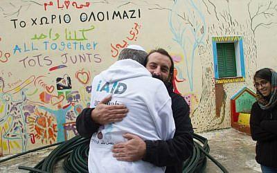 Rabbi Shu Eliovson receives a hug from Thanasis Voulgarakis at the Pikpa refugee camp in Mytilene, Lesbos, Greece. January 19, 2017. (Nave Antopolsky/iAID)