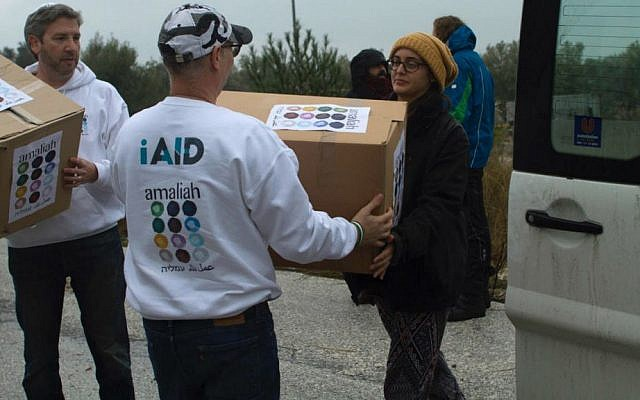 Rabbi Shu Eliovson (left) and Moti Kahana (center) unload relief supplies collected in Israel for refugees with Molly Nixon of Lifting Hands International in Lesbos, Greece. January 19, 2017. (Nave Antopolsky/iAID)