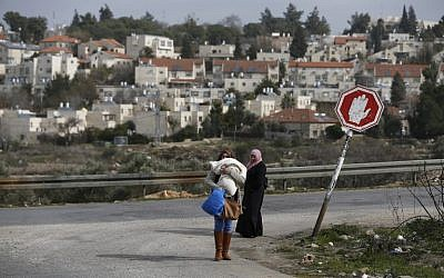Illustrative: Palestinian women from the Jalazoun refugee camp stand at a crossroad in the West Bank city of Ramallah with the Israeli settlement of Beit El seen behind them, on January 25, 2017. (AFP/Abbas Momani)