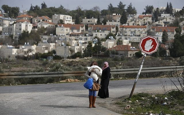 Palestinian women from the Jalazoun refugee camp stand at a crossroad in the West Bank city of Ramallah with the Israeli settlement of Beit El seen behind them, on January 25, 2017. (AFP/Abbas Momani)