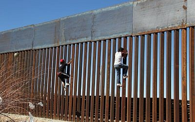 Boys play around, climbing the border division between Mexico and the US in Ciudad Juarez, Mexico on January 26, 2017. (AFP PHOTO / HERIKA MARTINEZ)