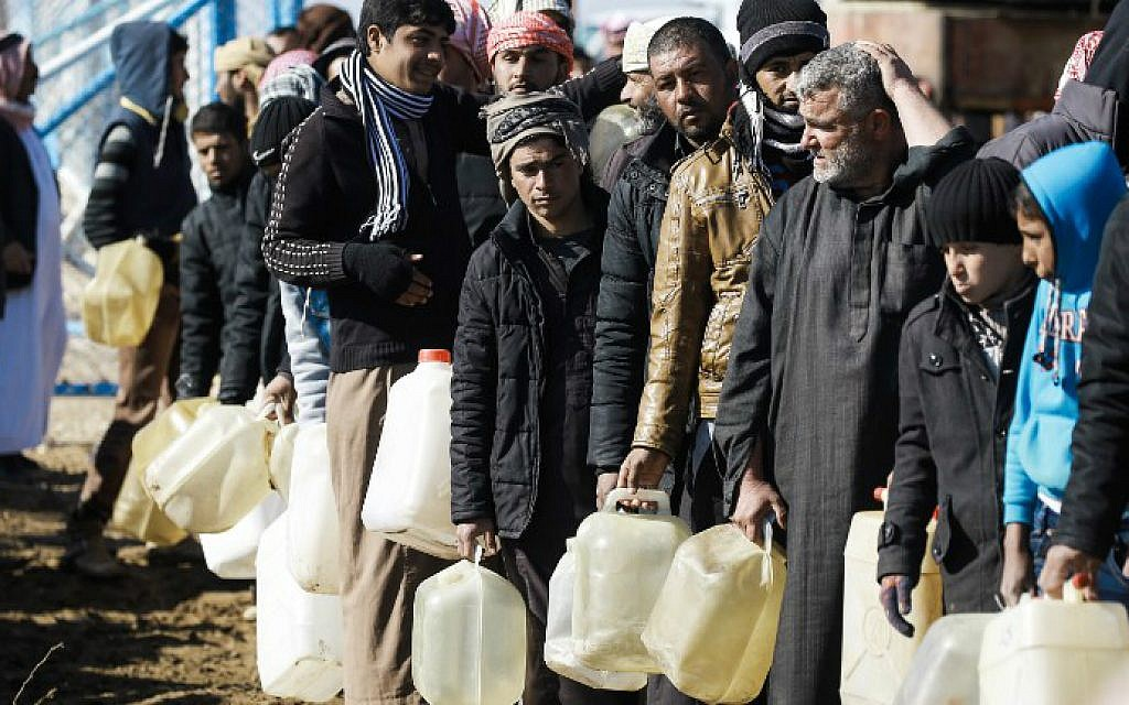 Refugees who fled the Iraqi city of Mosul due to the fighting between government forces and Islamic State (IS) group jihadists, queue for heating fuel at the UN-run al-Hol refugee camp in Syria's Hasakeh province, on January 29, 2017. (Delil Souleiman/AFP)