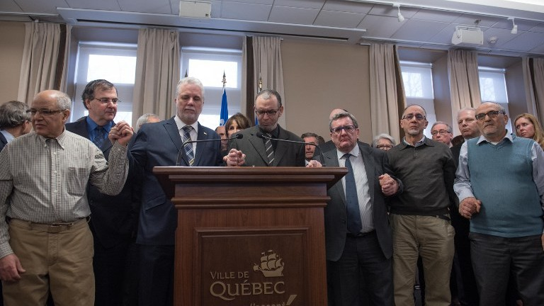 """L-R:Salah Benrekik, member of the association """"Ben Air""""; Francois Blais Quebec Education Minister ; Philippe Couillard, Quebec prime minister; Mohamed Yangui, president of the Islamic Cultural Center of Quebec, Regis Labeaume, Quebec city mayor; Boufeldja Benabdallah, co-founder of the Islamic Cultural Center of Quebec and Mohamed Labidi, vice- president of the Islamic Cultural Center of Quebec hold hands in solidarity during a press conference January 30, 2017 at the city hall in Quebec City. (AFP Photo/Alice Chiche)"""