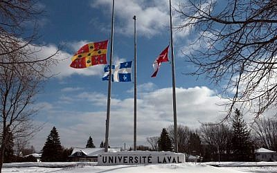 The flags (L-R) of Universite Laval, Quebec and Canada are at half-mast on campus January 31, 2017 in Quebec City, Quebec. (AFP Photo/Alice Chiche)
