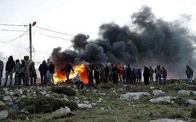 Opponents of the evacuation of the illegal Amona outpost set tires ablaze at Amona, northeast of Ramallah, on February 1, 2017. (AFP Photo/Jack Guez)