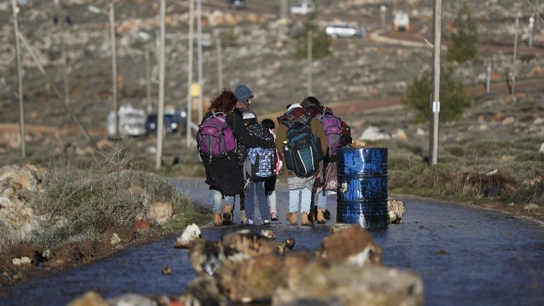 Jewish settlers walk with backpacks at the Amona outpost, northeast of Ramallah, on February 1, 2017. (AFP Photo/Thomas Coex)