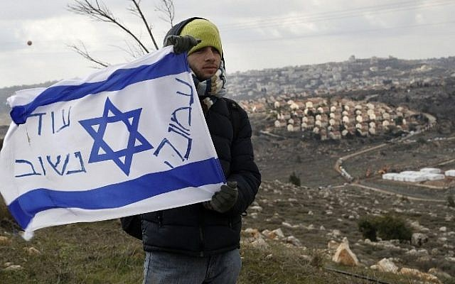 "An Israeli settler holds a flag with with ""Amona, we will return"" written on it at the Amona outpost, northeast of Ramallah, on February 1, 2017, ahead of its evacuation. (AFP Photo/Jack Guez)"