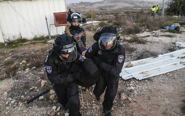 Israeli security forces carry a settler away as they evict residents from the illegal Amona outpost, northeast of Ramallah, on February 1, 2017. (AFP PHOTO/Thomas COEX)