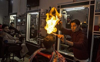 Ramadan Edwan, a Palestinian barber, uses fire in a hair-straightening technique with a client at his salon in the Rafah refugee camp, in the southern Gaza Strip on February 1, 2017. (Mahmud Hams/AFP)