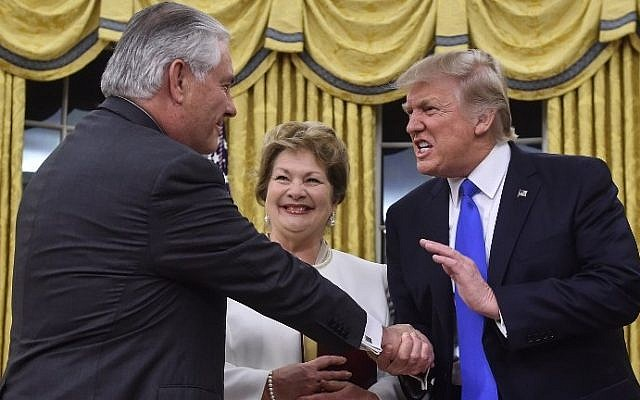 US President Donald Trump (R) shakes hands with Rex Tillerson (L) as Tillerson's wife Renda St. Clair looks on after Tillerson was sworn in as Secretary of State in the Oval Office at the White House in Washington, DC, on February 1, 2017. (AFP Photo/Nicholas Kamm)