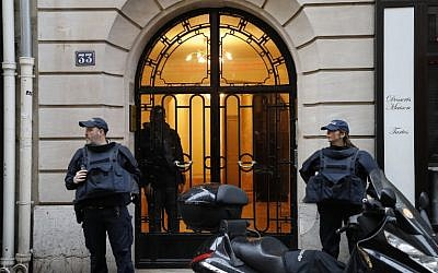 French police officers stand on a sidewalk as a search is conducted in Paris's 8th arrondissement as part of the investigation into the attack at the Louvre museum earlier on February 3, 2017. (AFP/Francois Guillot)